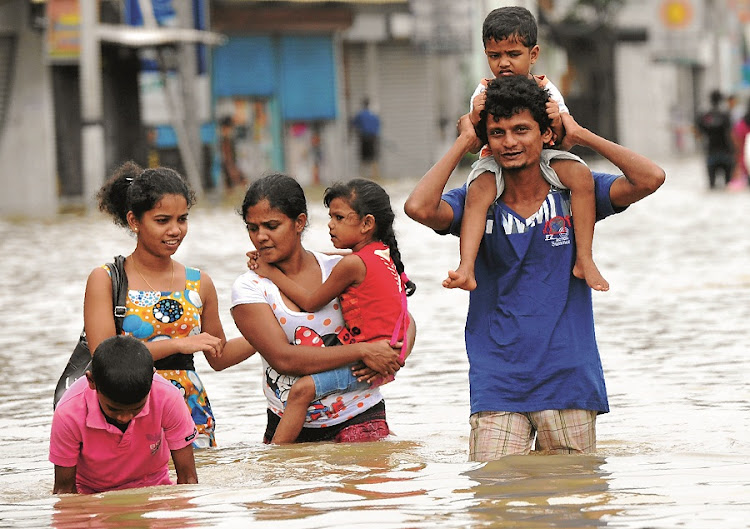 Sri Lankan residents make their way through floodwaters in the capital, Colombo. Two days of rain, which caused a landslide,  forced thousands to flee their homes. The navy and air force have helped with relief operations. Picture: GALLO IMAGES/AFP/LAKRUWAN WANNIARACHCHI