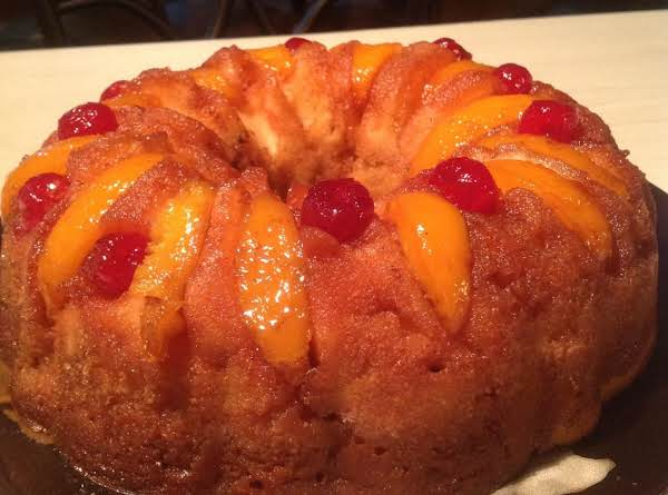 This Is An Upside-down Style Bundt Cake. The Cake Base Is A Light Recipe Pop Cake Topped With Cling Peaches And Cherries In A Brown Sugar Glaze.