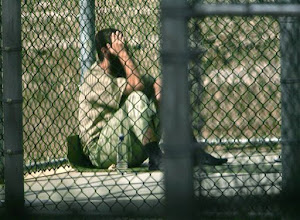 Photo: ** TO GO WITH GUANTANAMO HUNGER STRIKERS **  FILE  ** A Guantanamo detainee sits alone inside a fenced area during his daily outside period, at Guantanamo Bay U.S. Naval Base, Cuba. Twice a day at the U.S. military prison here, detainees Abdul Rahman Shalabi and Zaid Salim Zuhair Ahmed, who have refused to eat for nearly two years, are strapped to restraint chairs and force-fed to keep them alive. (AP Photo/Brennan Linsley, File)