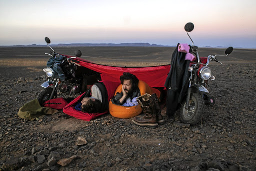 Adventurists rest under a makeshift tent on the Monkey Run in Morocco.