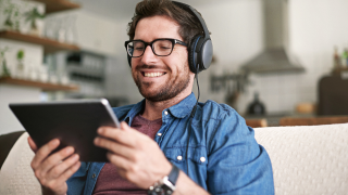 man with headphones on smiling at tablet