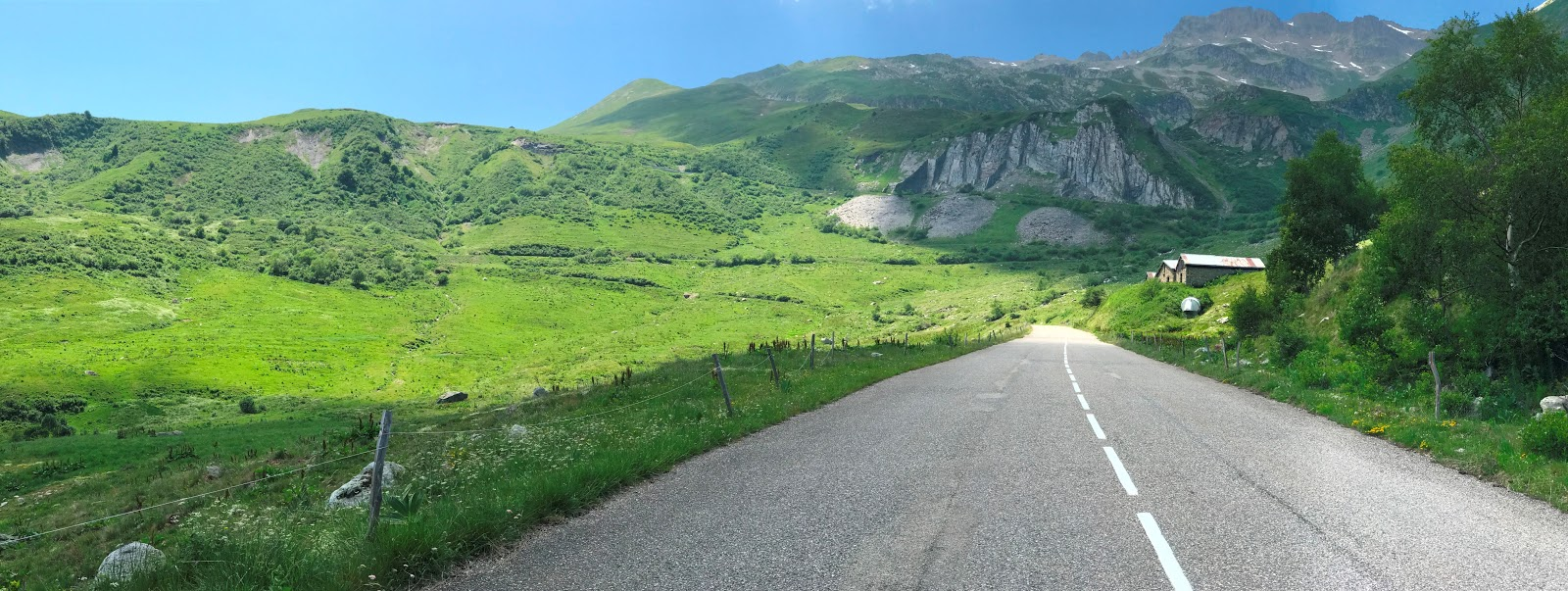 Cycling Col du Madeleiene - roadway and green fields with mountains in background