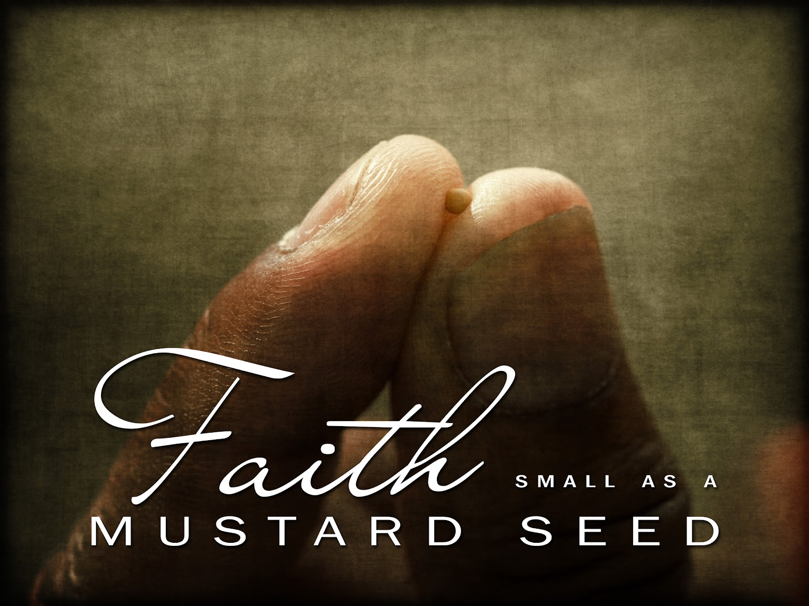 A mustard seed held between two finger tips.