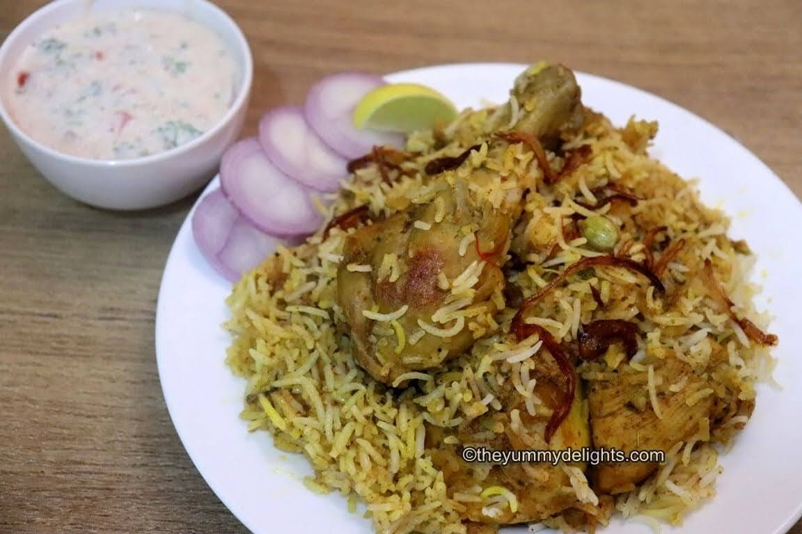image of kolkata style chicken biryani serve on a white plate. Served with raita, onion slices and lemon wedge on the side.