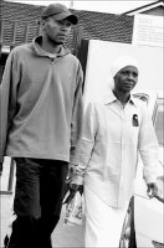 IN THE DOCK: Motshomagedi Mohlala and his mother, Joyce, on Monday outside court, where they appeared on charges of assault. Pic. Elijar Mushiana. 10/06/08. © Sowetan.