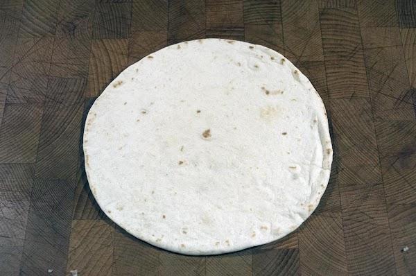 Place a flour tortilla on a flat surface.