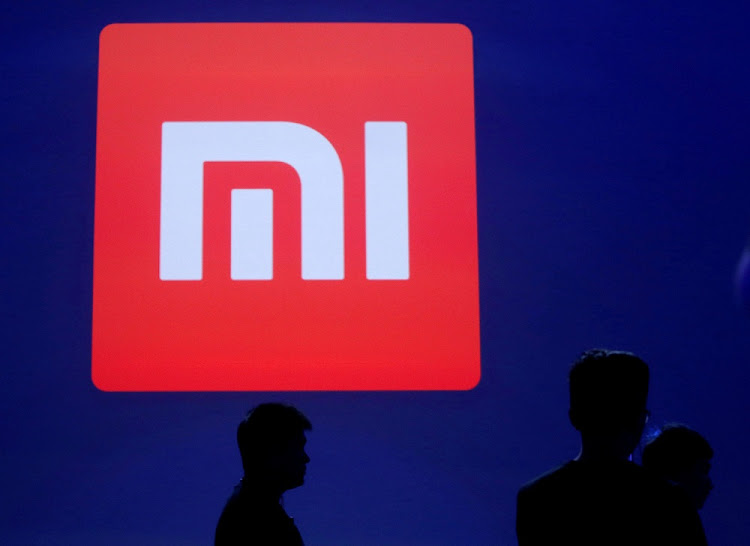 People  stand in front of Xiaomi's logo in Beijing. Picture: REUTERS