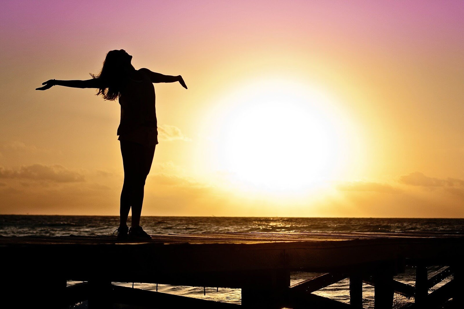 woman raising arms to sky standing on pier