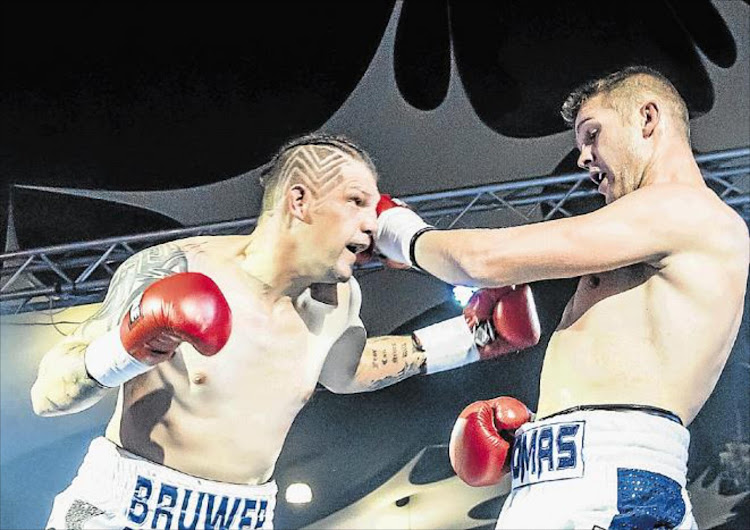 A file picture of Thomas Oosthuizen (left) and Daniel Bruwer exchanging blows during a WBA Pan-African light-heavyweight championship clash.
