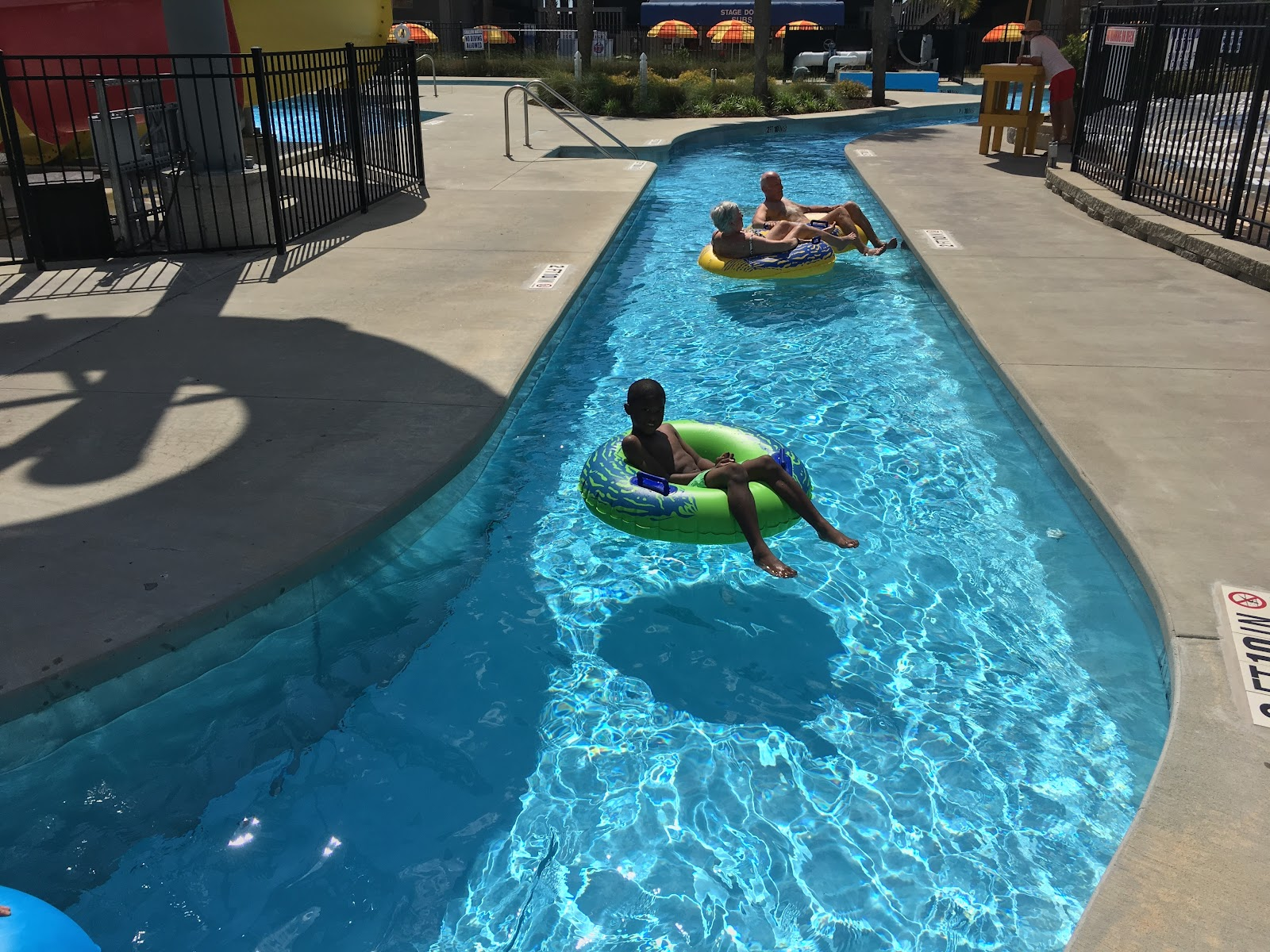 Child and a couple adults lounging in rafts in a lazy river pool