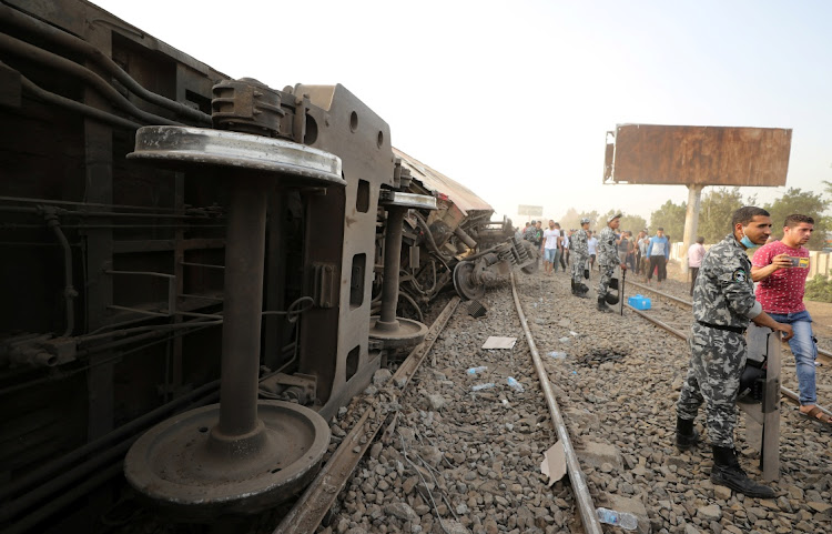 Egyptian police officers stand guard at the site where train carriages derailed in Qalioubia province, north of Cairo, Egypt on April 18, 2021.