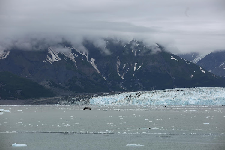 A tour boat glides by Hubbard Glacier during Oosterdam's Inside Passage cruise to Alaska.