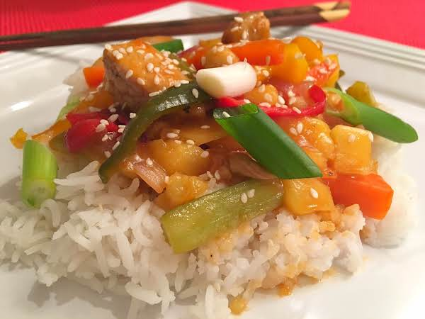 A Mixture Of Pork, Green Onions, Pineapple Chunks And Bell Peppers On A Bed Of Rice On A White Plate With Chop Sticks.