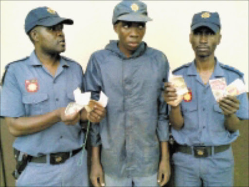 GOTCHA: Inspector Lazarus Msiza, left, and Captain Carter Monoge, right, of the Macadamia Border line flank a fake cop arrested on Tuesday. Pic: ANDREW HLONGWANE.  13/10/2009. © Sowetan.