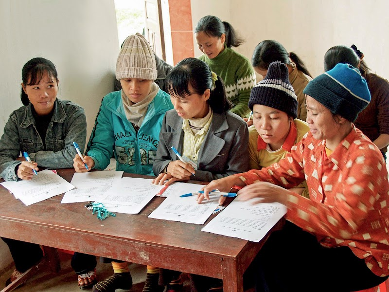 Group of women in Southeast Asia working together at a table with pens and papers.