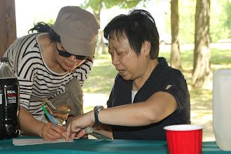 Photo: Mrs. Zheng helping receiving picnic payment