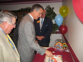 "Photo: Outgoing President Frank Dragoun, New President of the Rotary Club of DeBary cutting special ""Make Dreams Real"" installation night cake, and District Governor Bill Griffin"