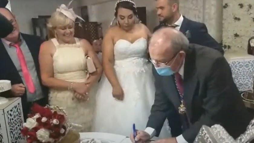 Bonilla firmando en presencia de los novios y otras personas sin mascarillas.
