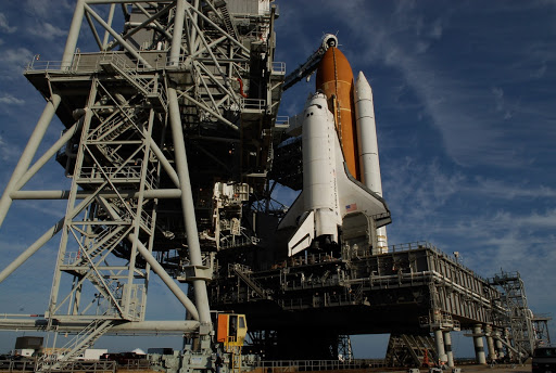 On Launch Pad 39A the rotating service structure is rolling to uncover space shuttle Endeavour.