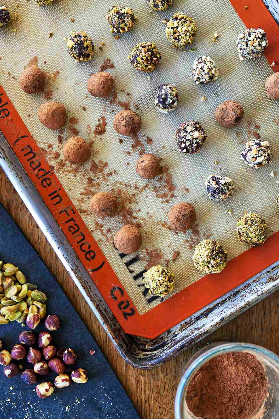 Chocolate balls on a baking sheet with nuts.
