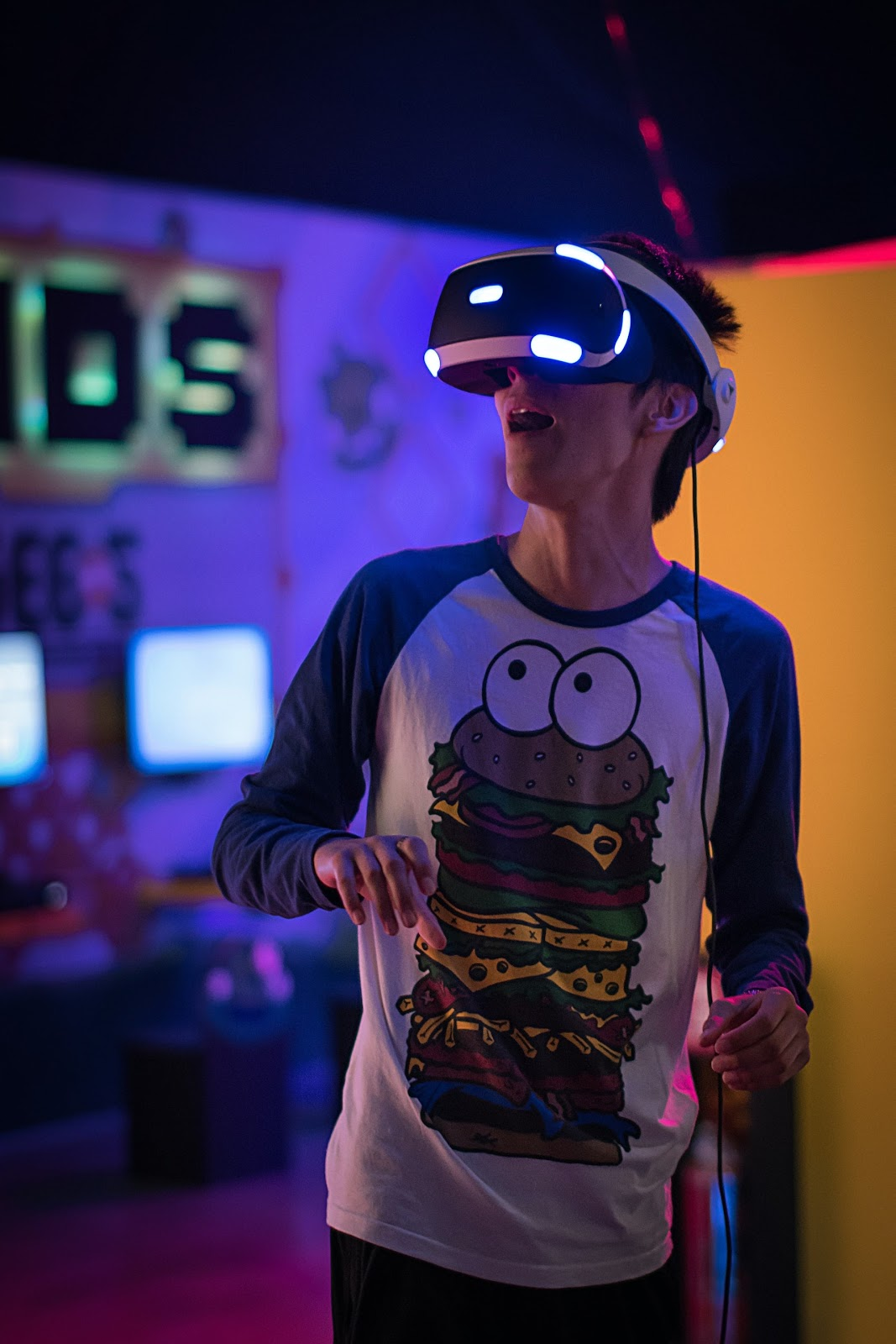 A boy wearing VR goggles, playing a game, to stay fit while also having fun