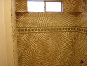 Photo: shower surround installation W/ 1x1 12' net and green glass tile border in the center by www.floorswedo.com