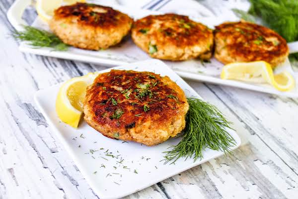 Canned Salmon Patty On A Plate With Lemon And Dill.