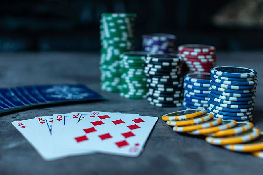 The ace, king, queen, jack, and ten of diamonds make a royal flush in front of piles of green, blue, black, red, and yellow poker chips