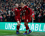 Virgil van Dijk of Liverpool celebrates after scoring his team's fifth goal with Andy Robertson of Liverpool during the Premier League match between Liverpool FC and Watford FC at Anfield on February 27, 2019 in Liverpool, United Kingdom.