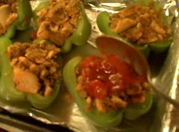 Using large serving spoon, scoop heaping spoonful of salsa on top of tamale-stuffed pepper...