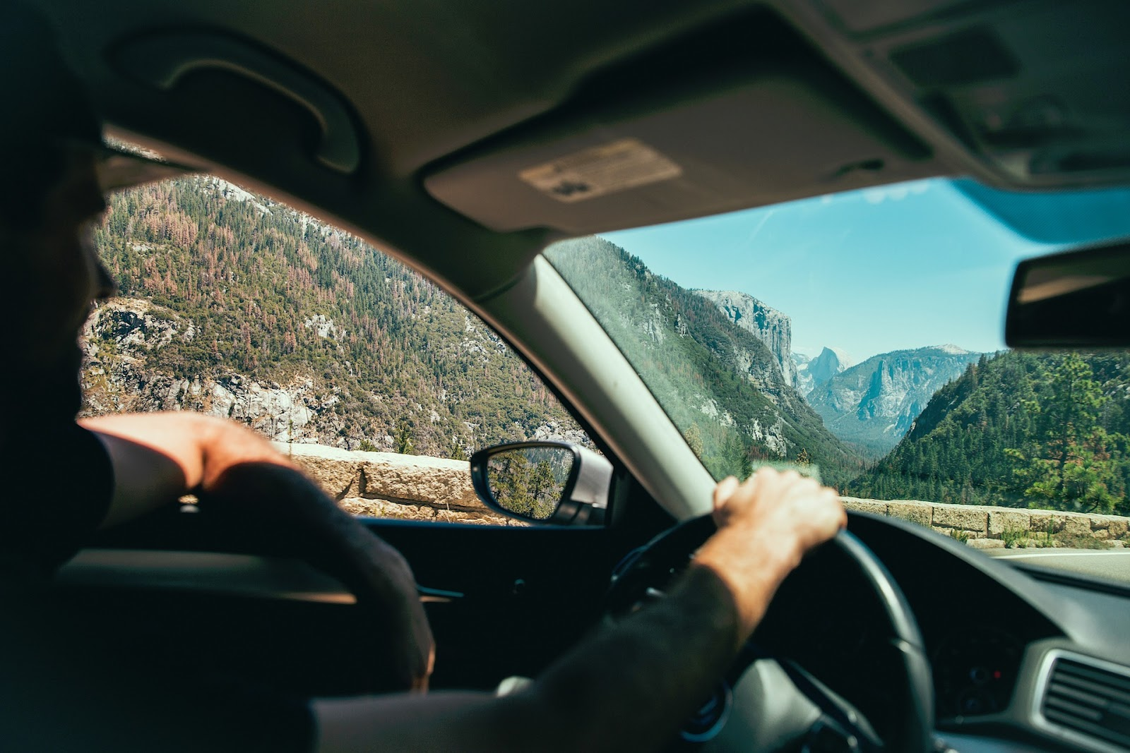 man driving car right hand on steering wheel left elbow out of the window driving through forest mountains nature