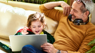 man and little girl look at tablet