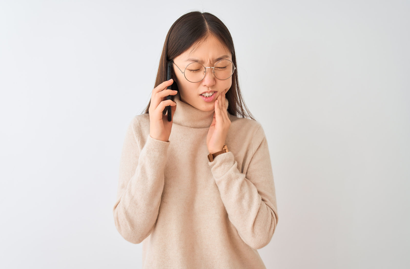 A Woman with a toothache on the phone calling to receive emergency dental care