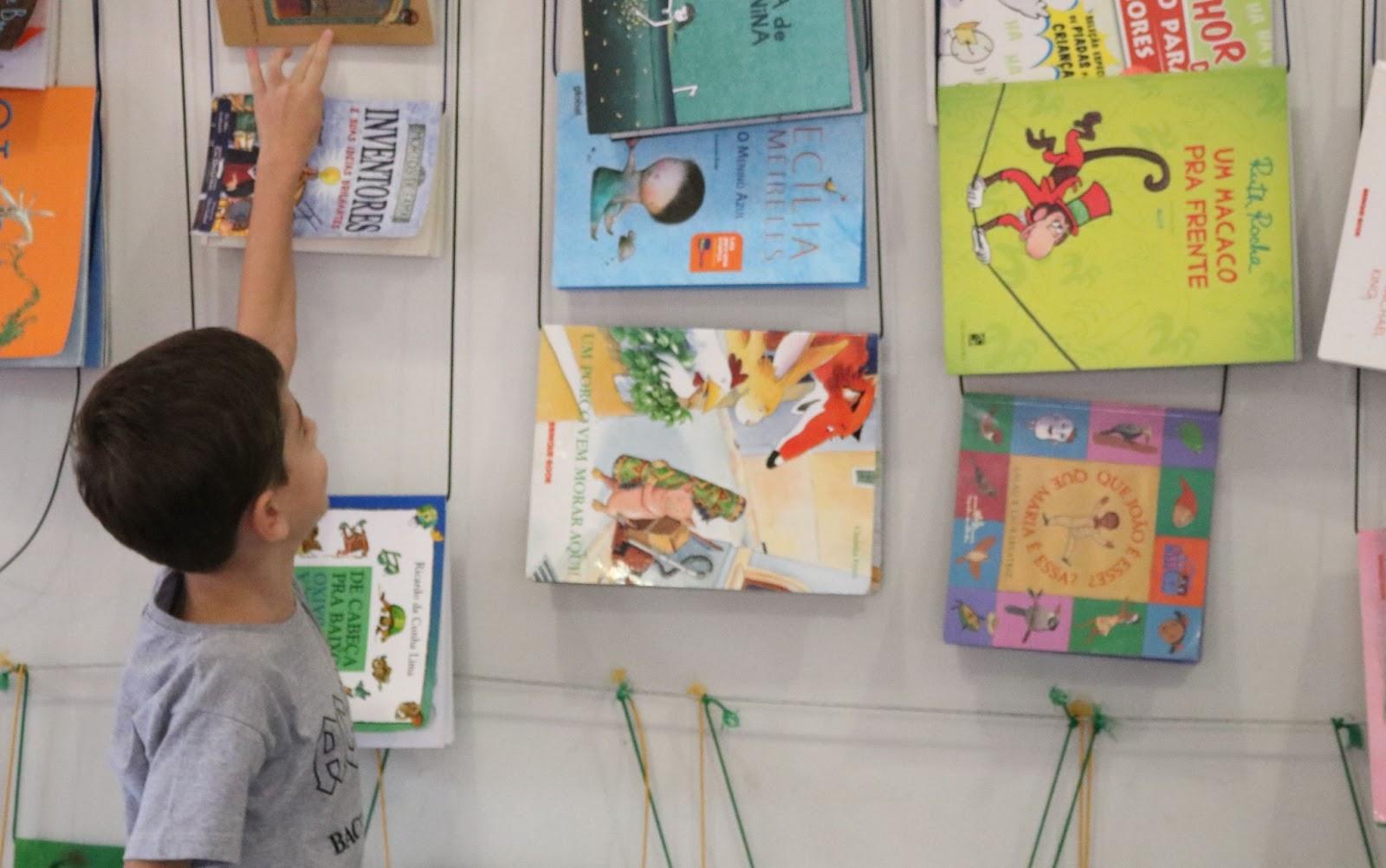 A imagem mostra uma exposição de livros em um cordão. Um menino, à frente, tenta alcançar um dos livros.