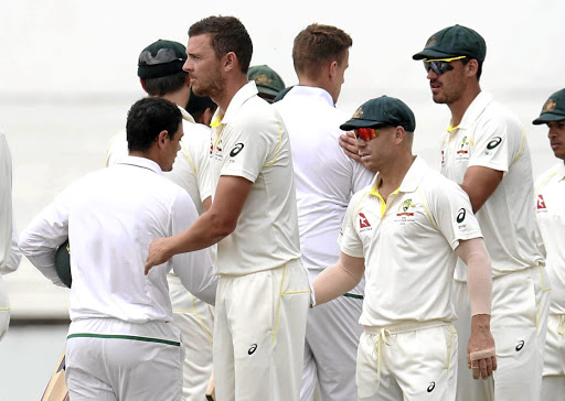 Quinton de Kock, left, shakes hands with David Warner, second right, at the end of the first Test in Durban on Monday. De Kock and Warner were involved in an altercation off the field on Sunday and a ruling is expected on Tuesday. Picture:MUZI NTOMBELA/BACKPAGEPIX