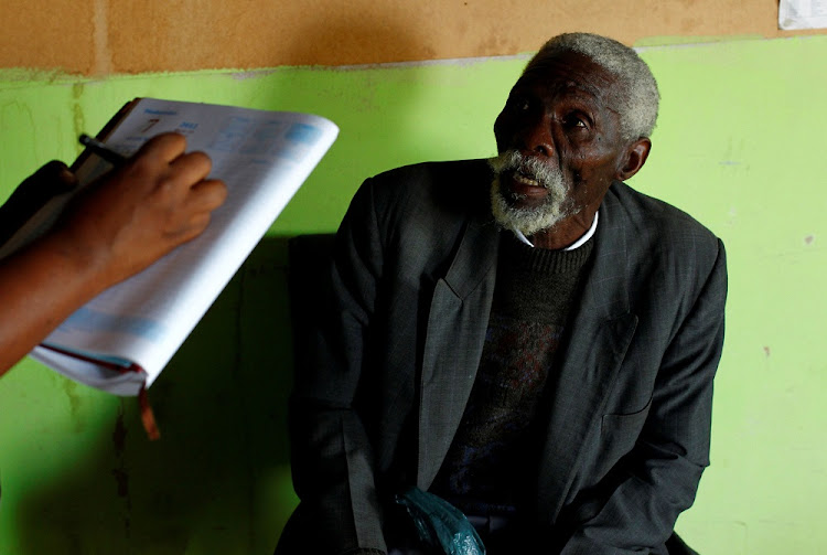 Former miner Senzele Silewise, 81, diagnosed with silicosis, talks to a paralegal in Bizana, Eastern Cape. Picture: REUTERS
