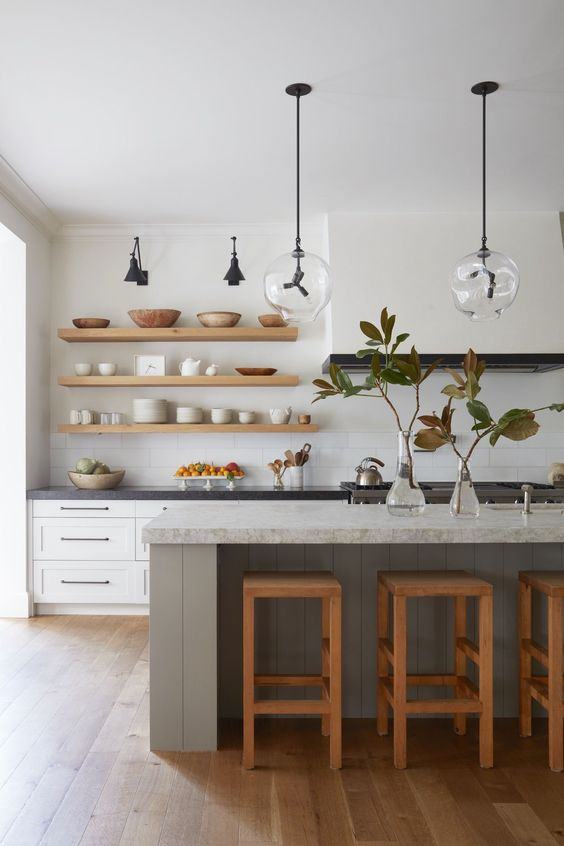 large modern scandinavian kitchen design with grey center island, white shaker cabinets, custom wood floating shelves, wood floors and modern glass pendant lights