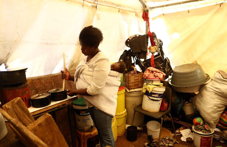 Nhlanhla Mabuza's little corner in the subdivided tent is crammed with buckets, stacked boxes, basins for washing, containers for water, a mattress and makeshift beds. Her cooking is done on a paraffin stove.