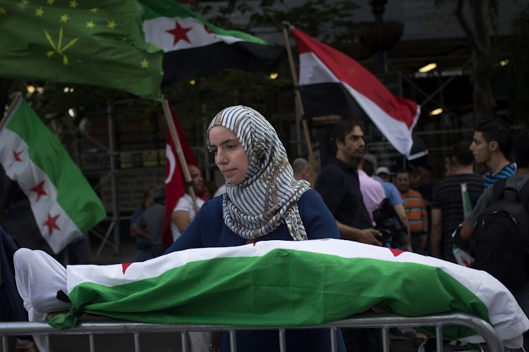 ATROCITY: Amina, a Syrian-Canadian, holds a mock corpse covered in Syria's flag during a protest in front of the United Nations building in New York. Picture: REUTERS