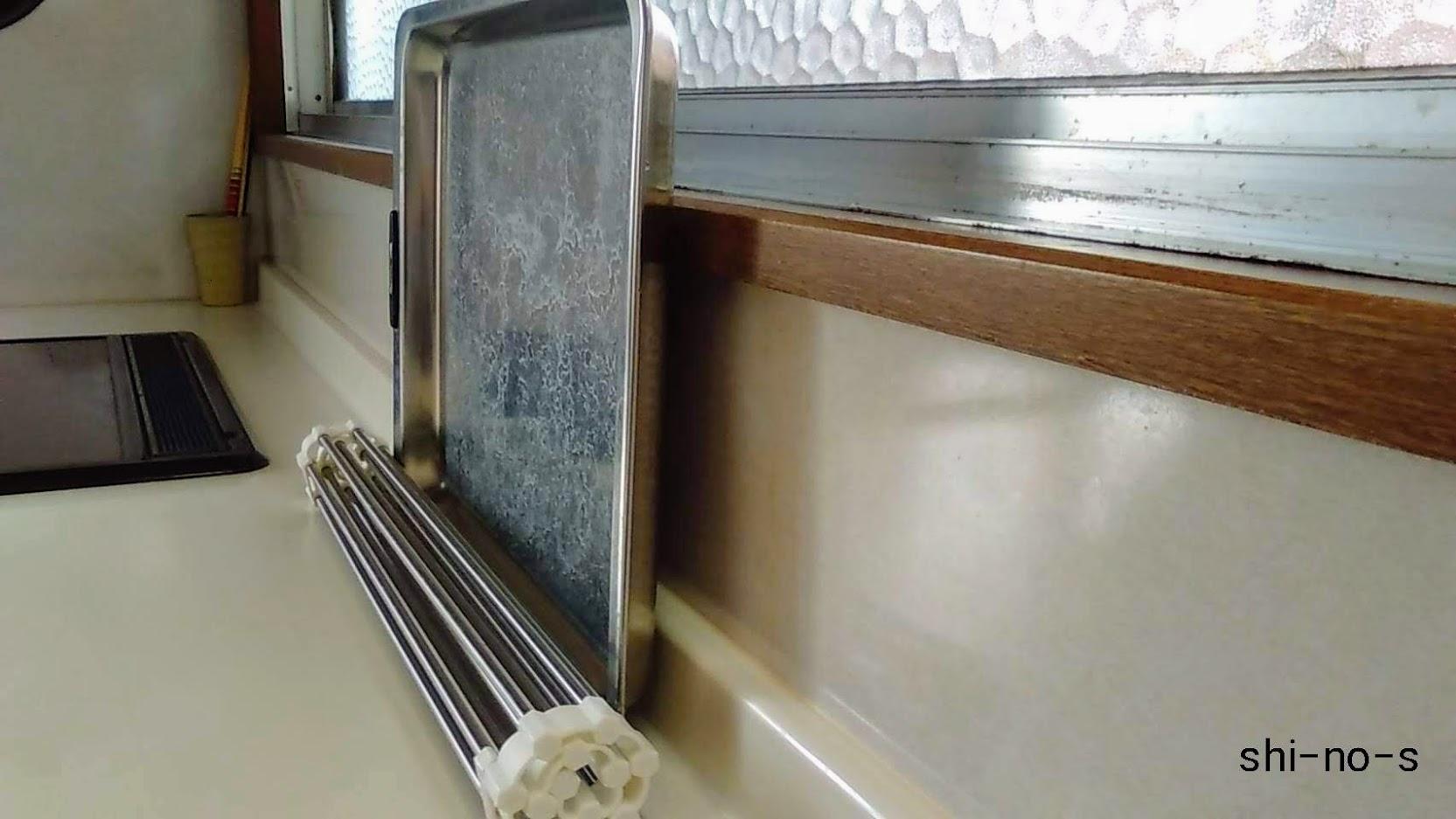 キッチン天板に丸められた水切りと、バッドが立て掛けてある