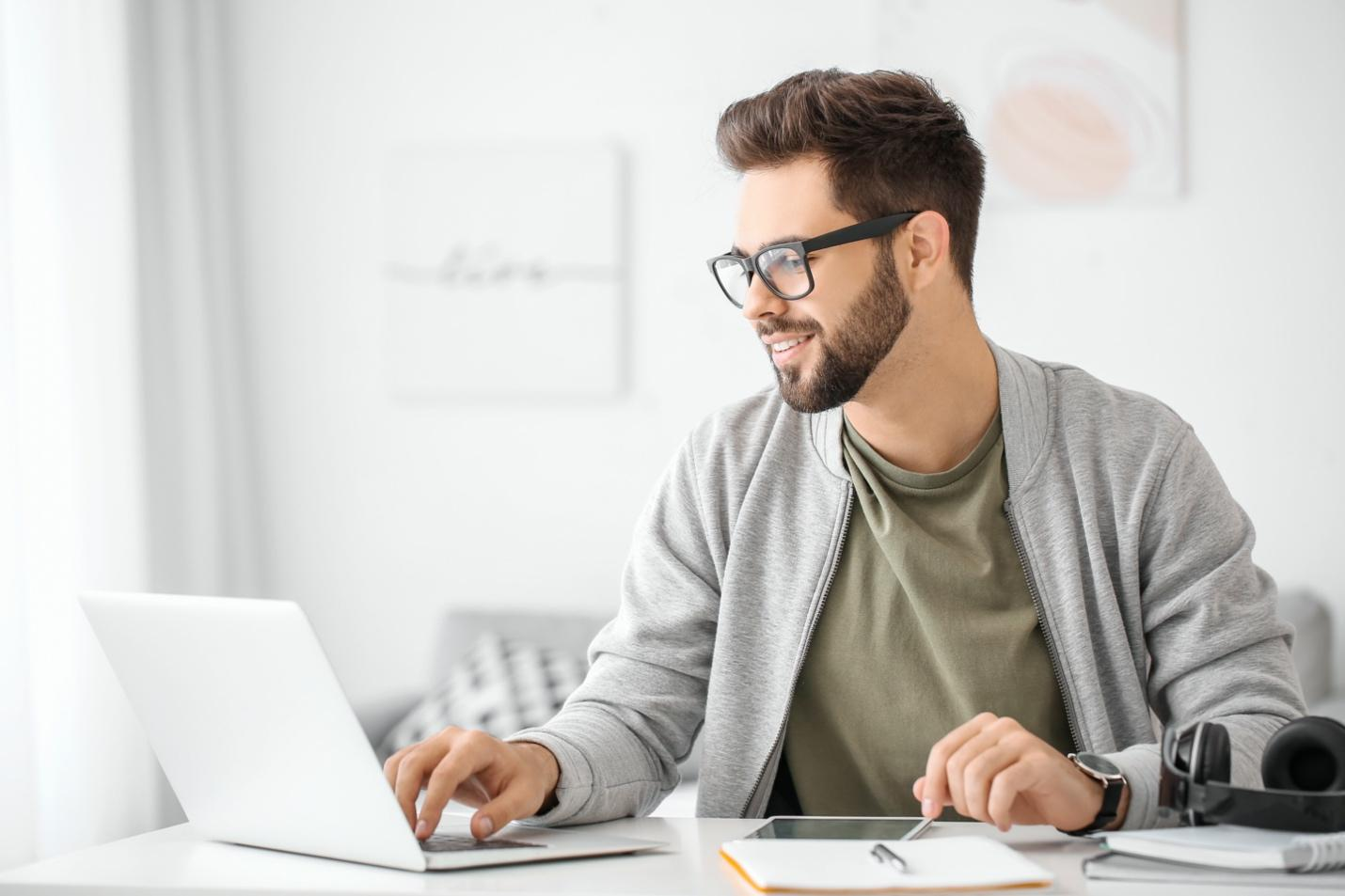 Man with digital skills in front of laptop and iPad.