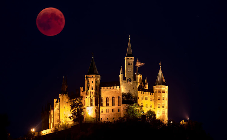 A Blood Moon rises behind The Hohenzollern Castle, the ancestral seat of the Prussian Royal House, on July 27 2018 in Hechingen, Germany.