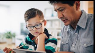 Un hombre mayor y un niño mirando un tablet