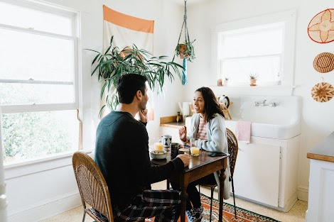 A man and woman in their pajamas talk at a small kitchen table and are undistracted by a phone.