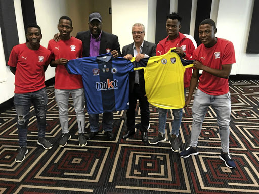 Jomo Sono and Morio Antonio Capuano (president of Gremio Football Club in Brazil) flanked by Cosmos' four under-17 players who have been signed by Capuano. /Mark Ogagan