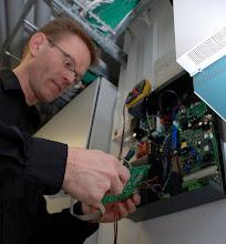Photo: Carsten monterer nyt telemodul i en alarm hos DS Flexhal