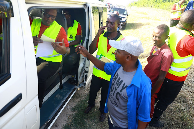 KFCB's Victor Okello issues a license to matatu driver Wycliff Osiemo at Bamburi Mtambo in Mombasa during a crackdown on Monday.