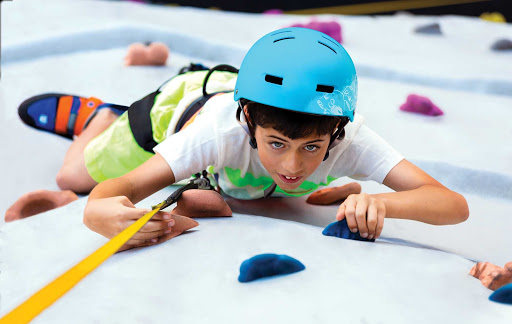 A kid tests his rock-climbing skills on Harmony of the Seas.