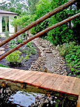 Photo: This raw-wood bridge leads over the end of the pond to a gazebo on stilts to tackle an area that floods every spring.