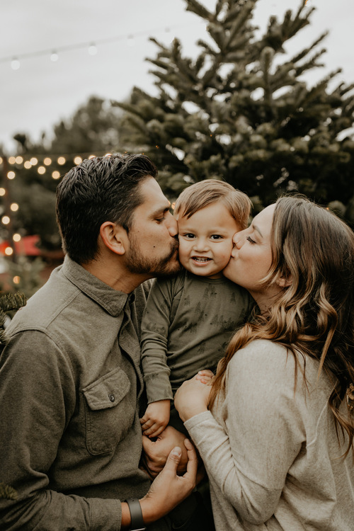 couple holding their son and kissing his cheek at the christmas tree grove